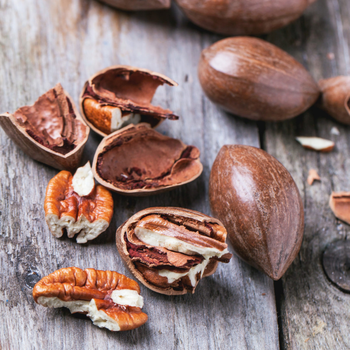 Whole and chopped pecan nuts on old wooden table. Square image