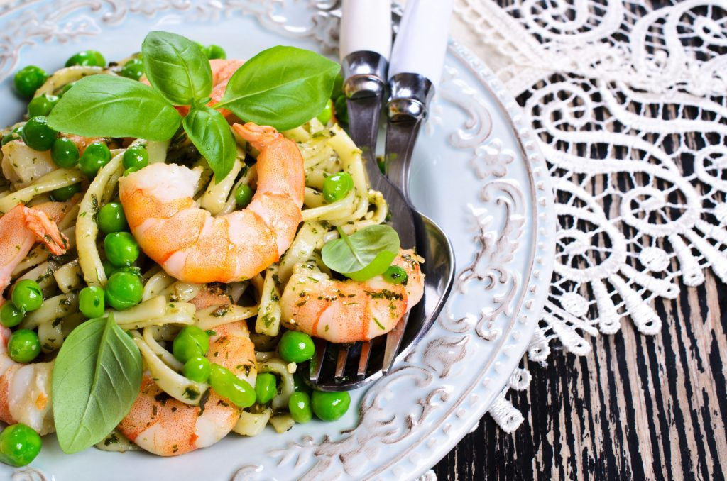 Pasta tagliatelle with shrimp and peas, dressed with pesto