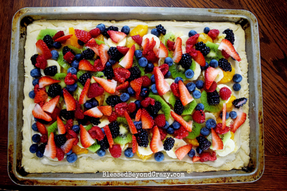 Layering fruit on top of The Ultimate Loaded Fruit Pizza