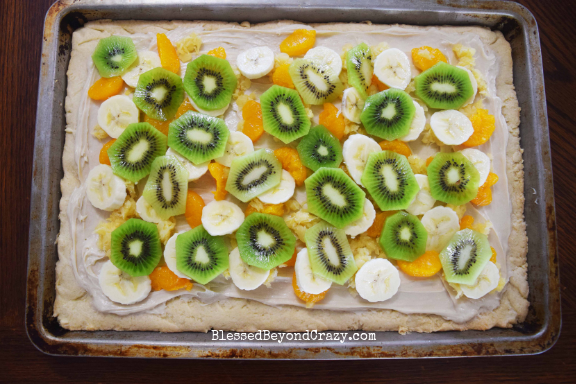 Layering Mandarin oranges, banana, and kiwi on The Ultimate Loaded Fruit Pizza