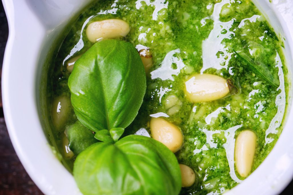 Close up of homemade pesto sauce with basil and pine nuts