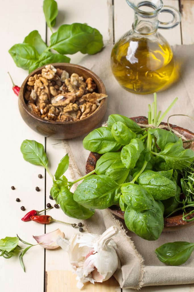 Bunch of fresh basil, bowl of walnuts, pepper, garlic and glass bottle of olive oil ready for 16 minute shrimp pasta meal